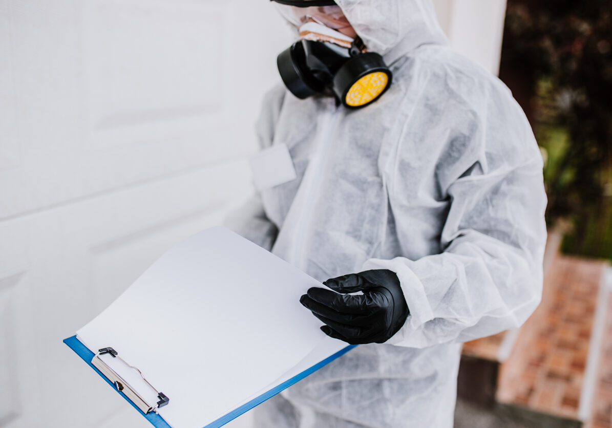 Professional worker in protective workwear reading checklist about house disinfection plan. Covid-19 and coronavirus pandemic concept.